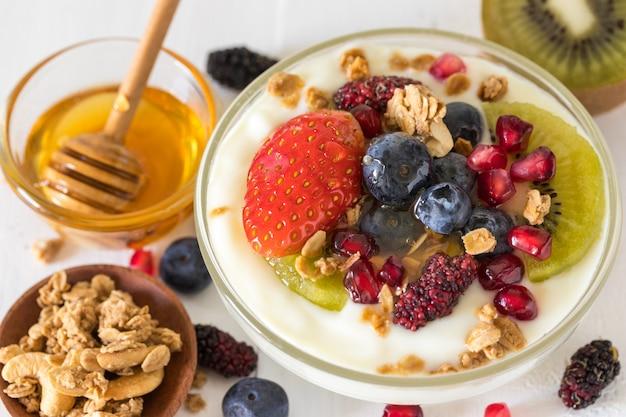 Plain yogurt with strawberry, blueberries, kiwi, granola, pomegranate in a glass bowl