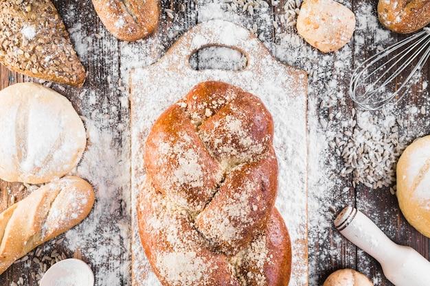 Плетеная буханка хлеба на разделочной доске с мукой над столом