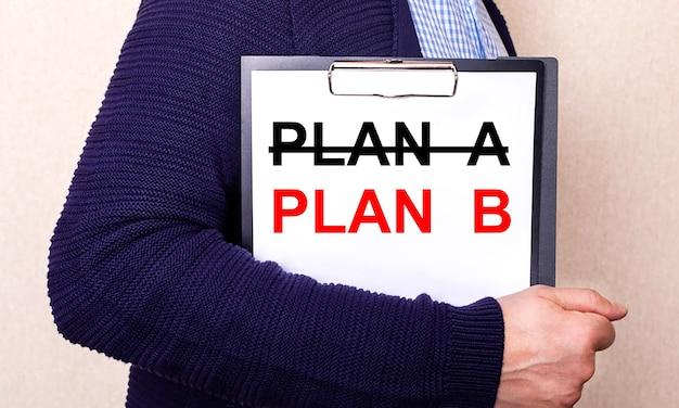 План б написан на белом листе, который держит человек, стоящий боком.