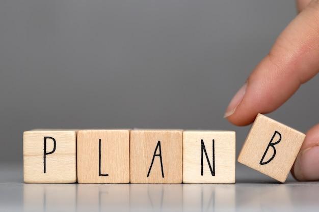 Деревянные кубики со словом plan b на сером фоне и человеческий палец, фон бизнес-концепции