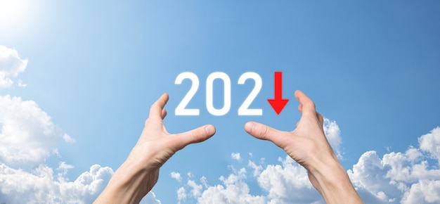 Планируйте отрицательный рост бизнеса в концепции 2021 года. план бизнесмена и увеличение отрицательных показателей в его бизнесе, снижение бизнес-концепций. держитесь за руку на фоне неба.