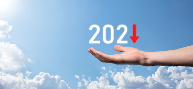 Plan business negative growth in year 2021 concept. businessman plan and increase of negative indicators in his business, decline down business concepts.hand hold on sky background.