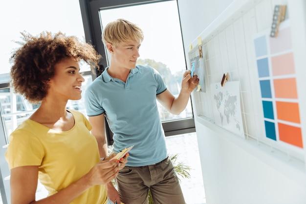 모든 것을 미리 계획하십시오. 사무실에 서서 추가 작업을 계획하는 동안 스티커 메모를 사용하는 즐거운 젊은 전문 동료