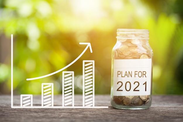 Планируйте на 2021 год слово с монетой в стеклянной банке и график вверх. финансовая концепция