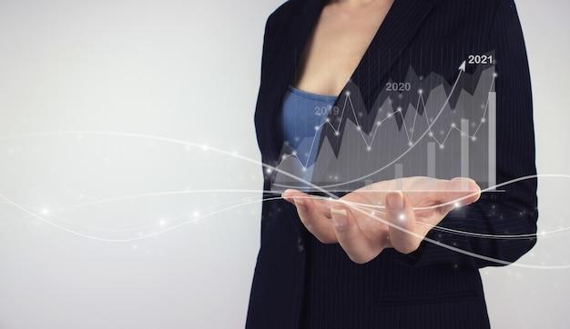 긍정적인 지표 개념의 성장 및 증가를 계획합니다. 회색 배경에 다이어그램이 있는 디지털 홀로그램 외환 차트를 손에 들고 있습니다. 사업 전략. 디지털 마케팅.