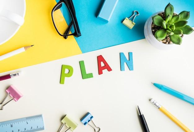 План слово на фоне офиса стол с поставками. красочный бизнес рабочий стол. концепции маркетинга