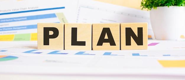 나무 조각에 단어를 계획하십시오. 배경은 비즈니스 그래프입니다. 비즈니스 및 금융 개념
