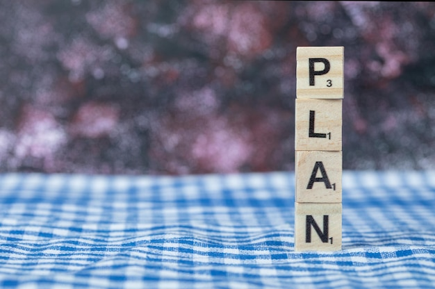 Plan writing with black letters on wooden dices on blue checked towel. high quality photo