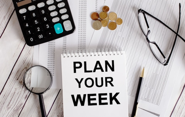 Plan your week written in a white notepad near a calculator, cash, glasses, a magnifying glass and a pen.