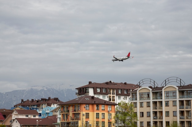 The plane arrived in the city. the airbus flies over the roofs of houses. adler district of sochi, russia. concept: vacation has begun
