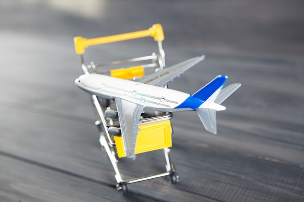 The plane in the basket. airline ticket purchase concept on gray wooden