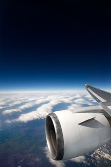 A plane engine up in the sky with the earth and blue sky in the background
