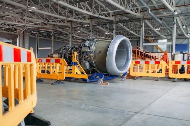 Двигатель самолета без крышек, обслуживание в ангаре