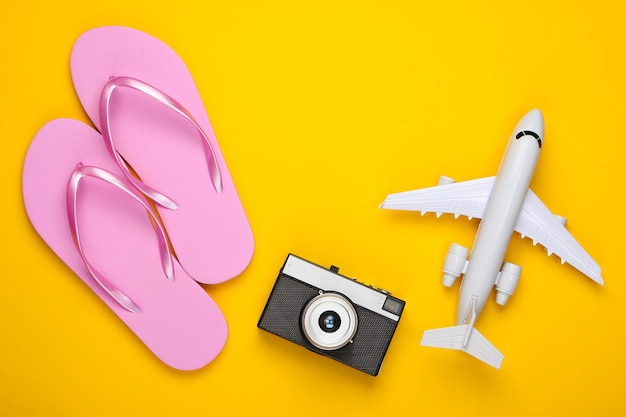 Фигурка-самолет, шлепки, фотоаппарат на желтом.