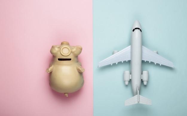Plane figurine, piggy bank on pink-blue pastel.