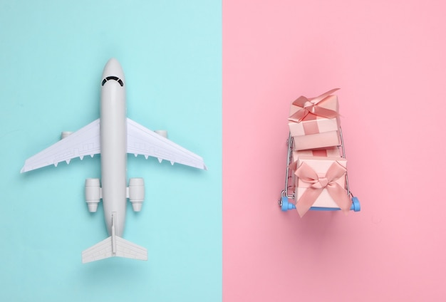 Plane figurine, shopping trolley and gift boxes on blue pink pastel. flat lay.
