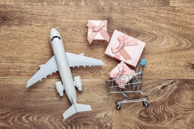 Plane figurine, shopping trolley and gift boxes on wooden floor. flat lay.