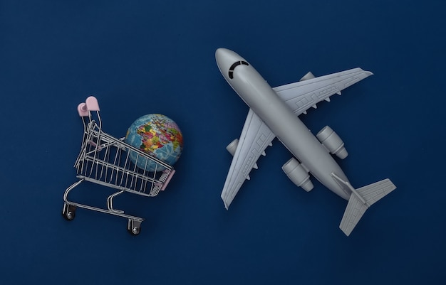 Plane figurine and shopping trolley with globe on classic blue background. delivery. color 2020. top view.