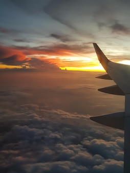 The plane flies over the clouds at an orange sunset view through the porthole