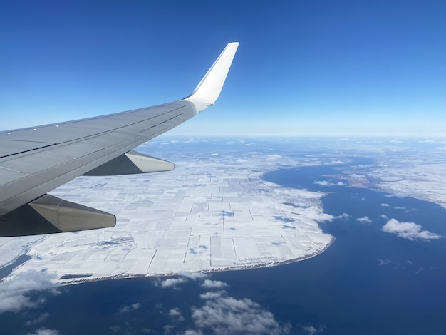 Plane flying over snow-covered ground