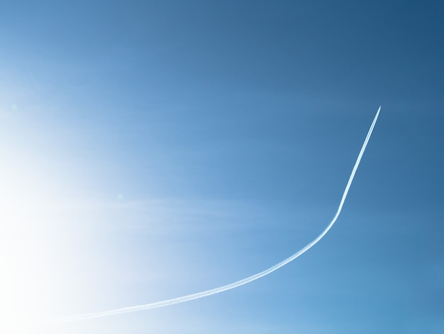 Plane flying up and leaving trail at blue sky background
