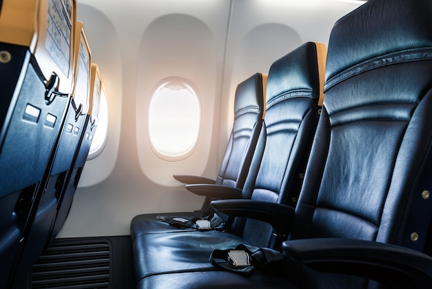 Plane interior - cabin with modern leather chair for passenger of airplane.