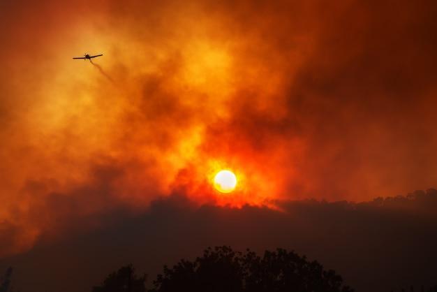 산불 진압을 위해 화학 물질의 흔적을 남기는 비행기. 석양에 대한 극적인 붉은 연기