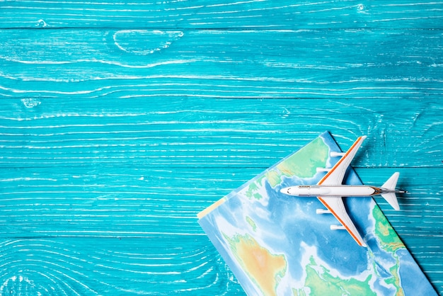 Plane and map located on blue wooden background