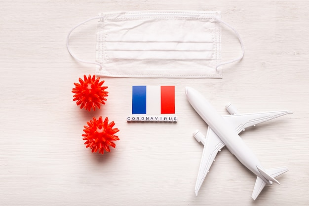 飛行機モデルとフェイスマスクとフランスの旗。コロナウイルスパンデミック。ヨーロッパとアジアからのコロナウイルスcovid-19による旅行者と旅行者のための飛行禁止と閉鎖国境。