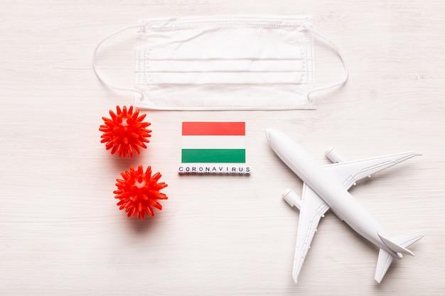飛行機のモデルとフェイスマスクとハンガリーの旗。コロナウイルスパンデミック。ヨーロッパとアジアからのコロナウイルスcovid-19による旅行者と旅行者のための飛行禁止と閉鎖国境。