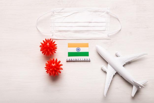 Модель самолета и маска для лица и флаг индии. коронавирус пандемия. запрет на полеты и закрытые границы для туристов и путешественников с коронавирусом ковид-19 из европы и азии.