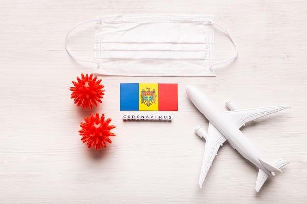 飛行機モデルとフェイスマスクとモルドバの旗。コロナウイルスパンデミック。ヨーロッパとアジアからのコロナウイルスcovid-19による旅行者と旅行者のための飛行禁止と閉鎖国境。