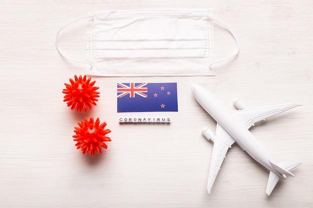 飛行機のモデルとフェイスマスクとフラグのニュージーランド。コロナウイルスパンデミック。ヨーロッパとアジアからのコロナウイルスcovid-19による旅行者と旅行者のための飛行禁止と閉鎖国境。