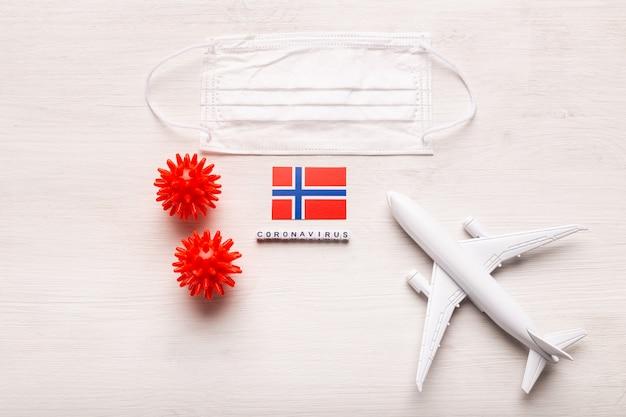 飛行機のモデルとフェイスマスクとノルウェーの旗。コロナウイルスパンデミック。ヨーロッパとアジアからのコロナウイルスcovid-19による旅行者と旅行者のための飛行禁止と閉鎖国境。