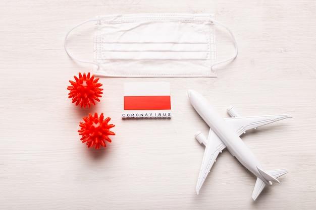 Модель самолета и маска для лица и флаг польши. коронавирус пандемия. запрет на полеты и закрытые границы для туристов и путешественников с коронавирусом ковид-19 из европы и азии.