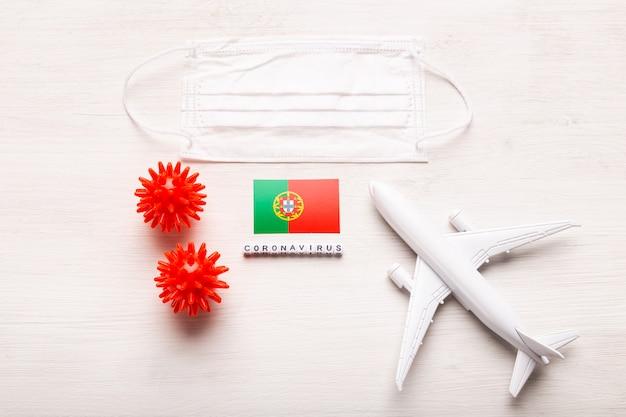 平面モデルとフェイスマスクおよびポルトガルの旗。コロナウイルスパンデミック。ヨーロッパとアジアからのコロナウイルスcovid-19による旅行者と旅行者のための飛行禁止と閉鎖国境。