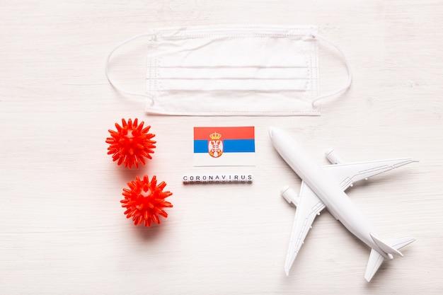 平面モデルとフェイスマスクとセルビアの旗。コロナウイルスパンデミック。ヨーロッパとアジアからのコロナウイルスcovid-19による旅行者と旅行者のための飛行禁止と閉鎖国境。