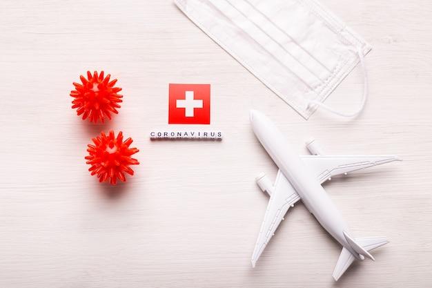 Модель самолета и маска для лица и флаг швейцарии. коронавирус пандемия. запрет на полеты и закрытые границы для туристов и путешественников с коронавирусом covid-19 из европы и азии.