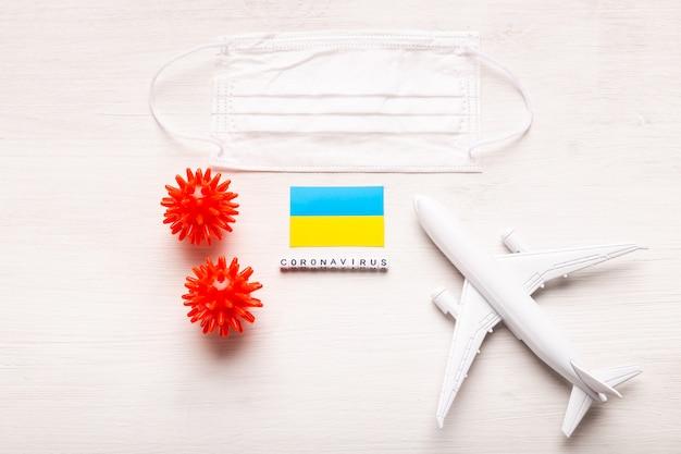 Модель самолета и маска для лица и флаг украины. коронавирус пандемия. запрет на полеты и закрытые границы для туристов и путешественников с коронавирусом ковид-19 из европы и азии.