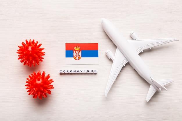 飛行機モデルとセルビアの旗。コロナウイルスパンデミック。ヨーロッパとアジアからのコロナウイルスcovid-19による旅行者と旅行者のための飛行禁止と閉鎖国境。