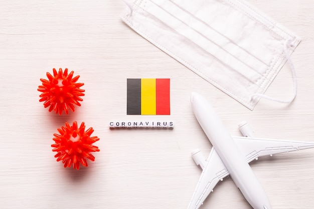 Plane model and face mask and flag belgium. coronavirus pandemic. flight ban and closed borders for tourists and travelers with coronavirus covid-19 from europe and asia.