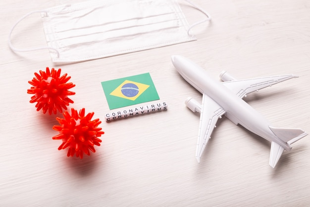 Plane model and face mask and flag brazil. coronavirus pandemic. flight ban and closed borders for tourists and travelers with coronavirus covid-19 from europe and asia.