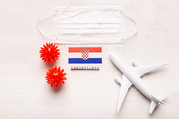 Plane model and face mask and flag croatia. coronavirus pandemic. flight ban and closed borders for tourists and travelers with coronavirus covid-19 from europe and asia.
