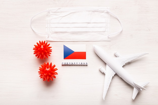 Plane model and face mask and flag czech republic. coronavirus pandemic. flight ban and closed borders for tourists and travelers with coronavirus covid-19 from europe and asia.