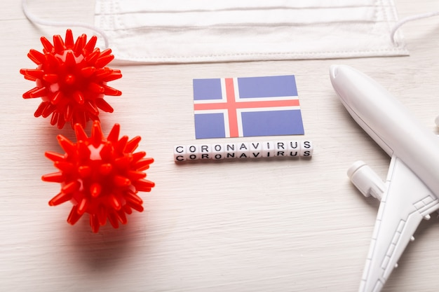 Plane model and face mask and flag iceland. coronavirus pandemic. flight ban and closed borders for tourists and travelers with coronavirus covid-19 from europe and asia.