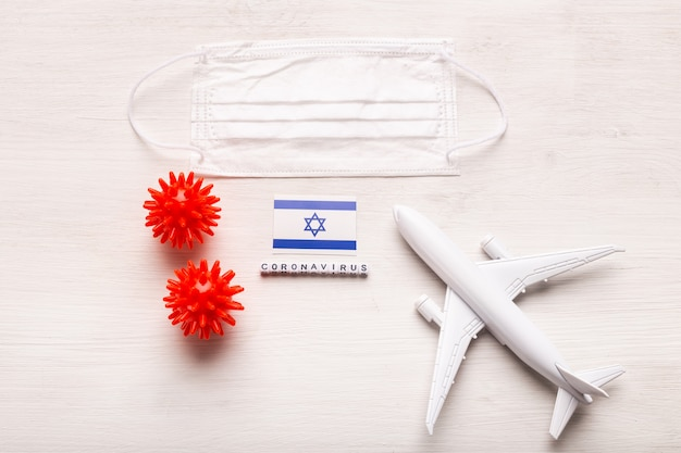 Plane model and face mask and flag israel. coronavirus pandemic. flight ban and closed borders for tourists and travelers with coronavirus covid-19 from europe and asia.