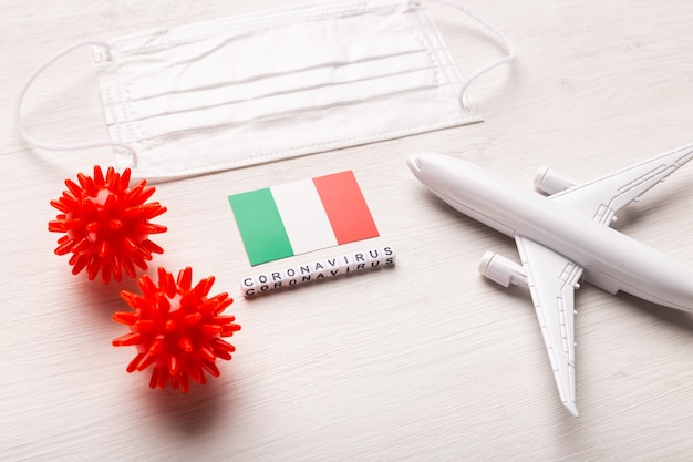 Plane model and face mask and flag italy. coronavirus pandemic. flight ban and closed borders for tourists and travelers with coronavirus covid-19 from europe and asia.