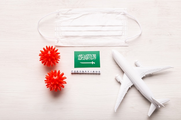 Plane model and face mask and flag saudi arabia. coronavirus pandemic. flight ban and closed borders for tourists and travelers with coronavirus covid-19 from europe and asia.