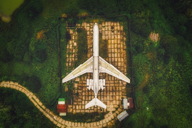 Plane model - museum on a concrete platform on the ground among the green forest