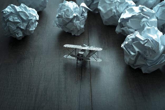Plane model with crumpled paper on wood background. business frustrations, job stress and failed exam .